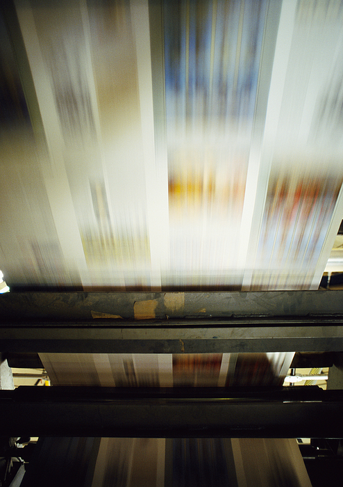 Printed paper on printing press, blurred motion Photograph by James Hardy