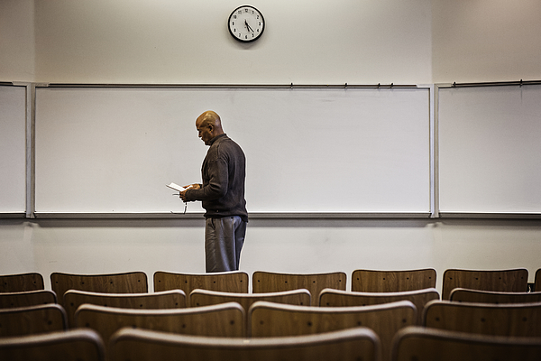 Professor standing in empty lecture hall Photograph by Hill Street Studios