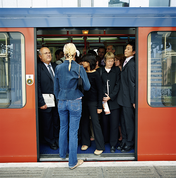 Rear View of a Blonde Woman Trying to Board a Crowded Train Photograph by Digital Vision.