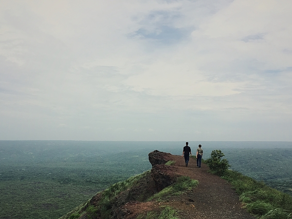 Rear View Of Men Walking On Cliff Against Cloudy Sky Photograph by Galen Dueck / EyeEm