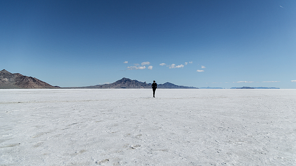 Rear View Of Person Standing On Salt Flat Against Sky Photograph by Alessandro Miccoli / EyeEm