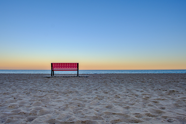 Red Empty Bench At The Beach At Sunset, Sand In Foreground And Ocean In Backround Photograph by Finn Bjurvoll Hansen