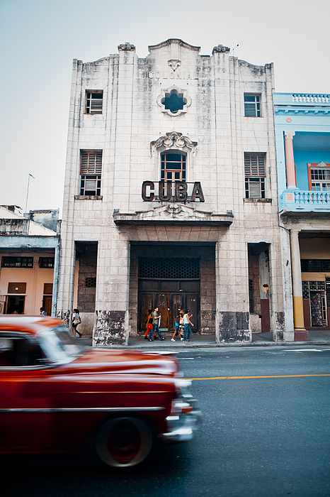 Red oldtimer car passing Cuba sign Photograph by Merten Snijders