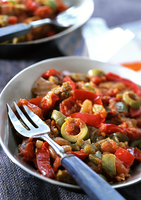 Red pepper and olive dish in bowl with fork, close-up Photograph by Jean-Blaise Hall