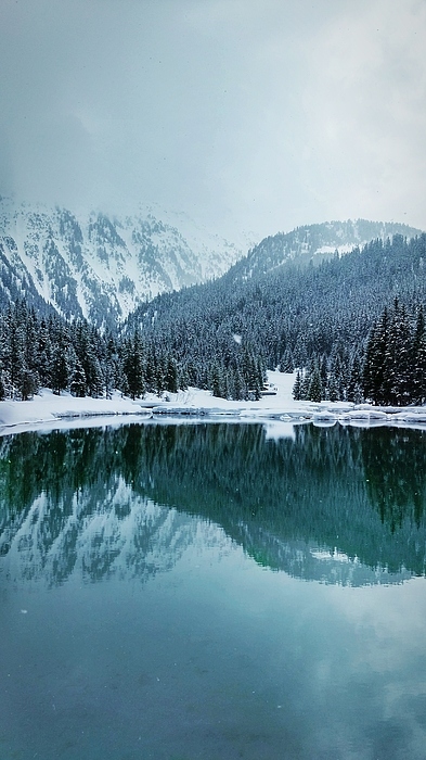 Reflection Of Mountains In Lake During Winter Photograph by Rmi Seznec / EyeEm