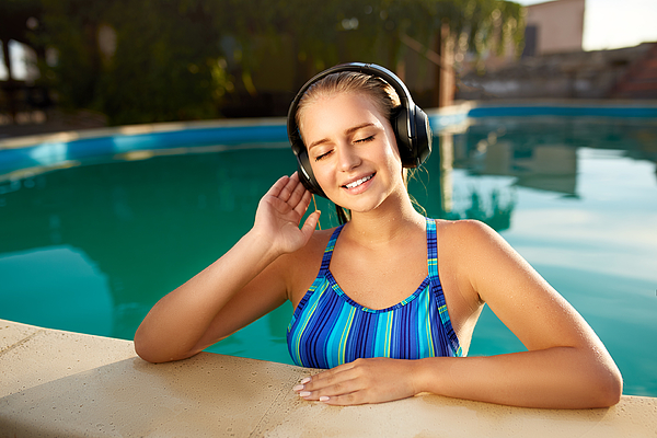 Relaxed smiling woman listening to music in headphones bathing in swimming pool. Blonde girl enjoys favourite song with goosebumps on skin. Waterproof headphones with touch control mobility concept Photograph by Artiemedvedev