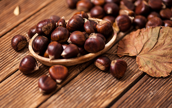 Ripe chestnuts in a frying pan on old wooden table close up with copy space. Roasted Chestnuts for Christmasn Photograph by Đorđe Banjanin