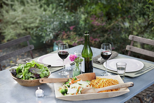 Salad and pasta on set table outdoors Photograph by Robert Nicholas