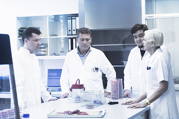 Scientists discussing in laboratory Photograph by Sigrid Gombert