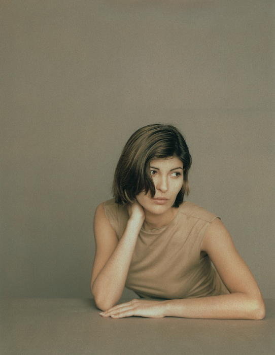Seated Woman With Elbows On Table, Leaning Forward With Hand Behind Neck, Portrait Photograph by Matthieu Spohn