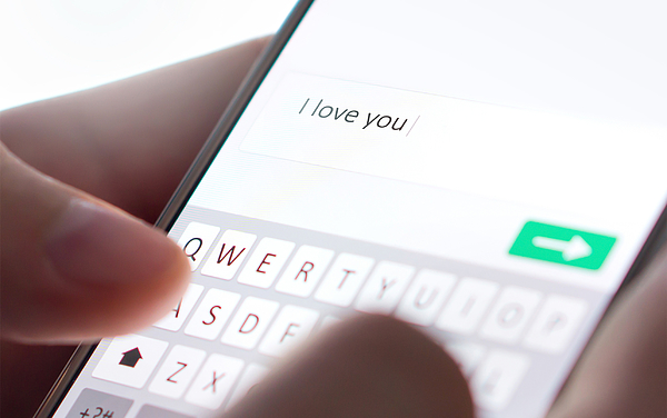 Sending I love you text message with mobile phone. Online dating, texting or catfishing concept. Romance fraud, scam or deceit with smartphone. Man writing comment. Photograph by Tero Vesalainen