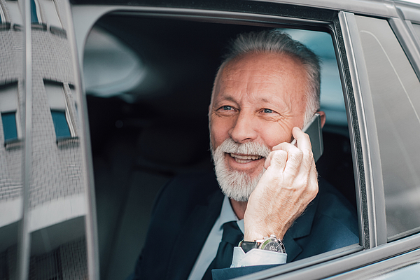 Senior Businessman Using Phone In Business Car Photograph by RgStudio