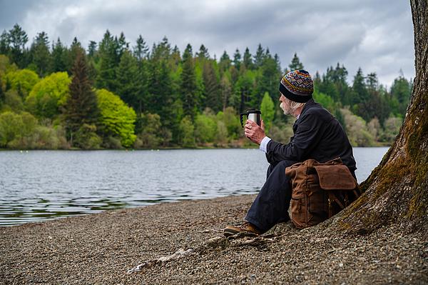 Senior man sitting beside a loch Photograph by JohnFScott