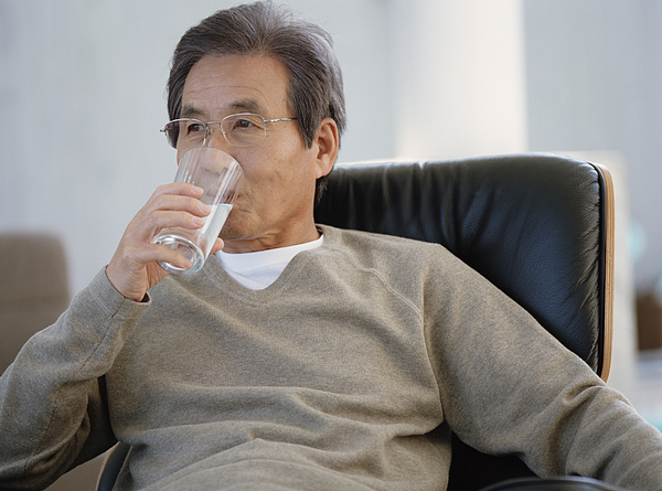 Senior man sitting on armchair drinking glass of water Photograph by Digital Vision