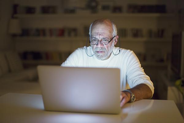 Senior man using a laptop Photograph by Thanasis Zovoilis