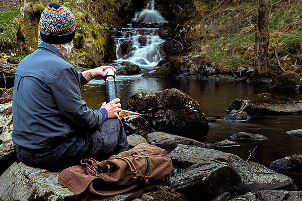Senior man with a thermos flask at a waterfall Photograph by JohnFScott