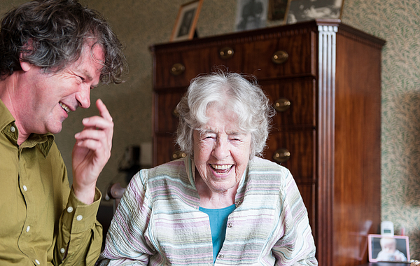 Senior woman and mature man laughing Photograph by Lucy Lambriex