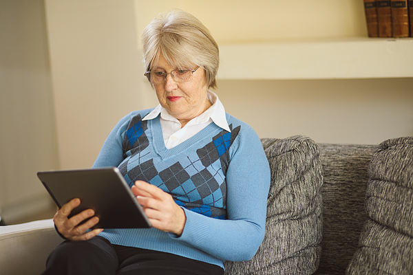 Senior woman using digital tablet at home Photograph by EmirMemedovski