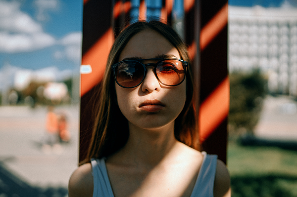 Shadowed portrait of young woman standing outside in sunglasses Photograph by Masha Raymers