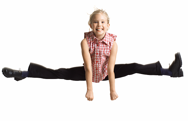 Silhouette Of A Caucasian Blonde Female Child  In Black Pants And A Plaid Shirt As She Jumps Up And Does The Splits Photograph by Photodisc