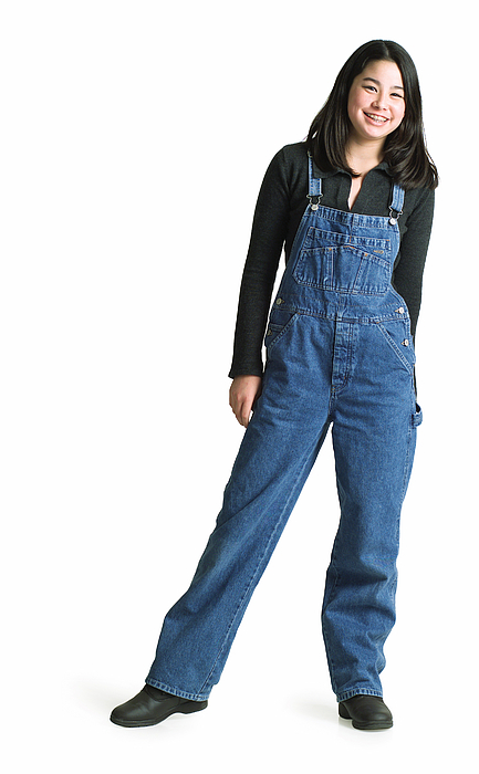 Silhouette Of An Asian Teenage Girl In Denim Overalls As She Smiles At The Camera Photograph by Photodisc