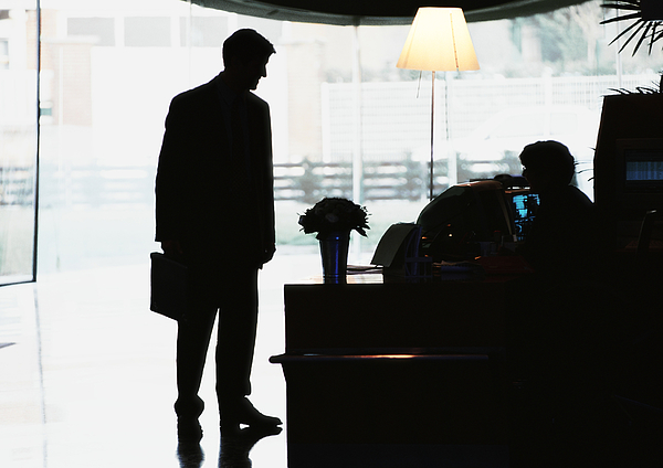 Silhouette Of Businessman Standing In Front Of Desk Photograph by Eric Audras