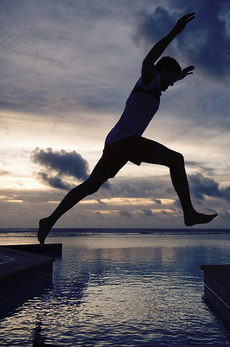 Silhouette of Caucasian man jumping over swimming pool at sunset Photograph by Jacobs Stock Photography Ltd