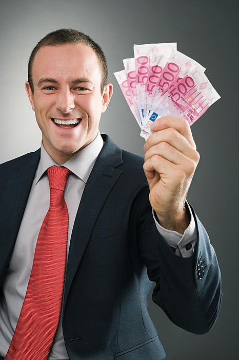 Smiling businessman with bank notes Photograph by Image Source