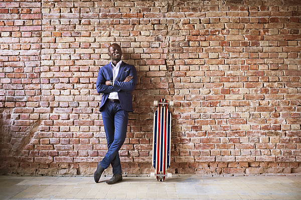 Smiling businessman with longboard at brick wall Photograph by Westend61