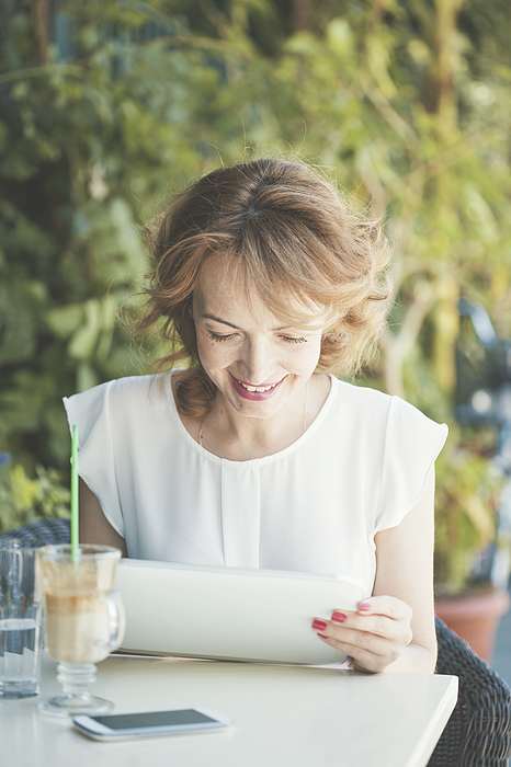 Smiling mid adult woman using digital tablet Photograph by Fotostorm