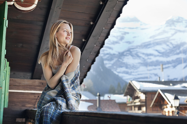 Smiling woman wrapped in a blanket and looking at view on cabin porch Photograph by Sam Edwards