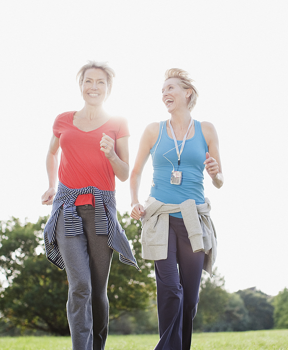 Smiling women jogging together Photograph by Robert Daly