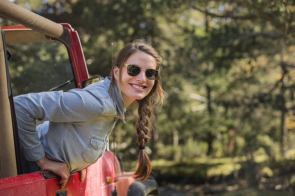 Smiling young woman leaning out of jeep Photograph by Morsa Images