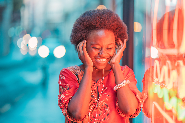 Smiling young woman with headphones standing next to neon light Photograph by Westend61