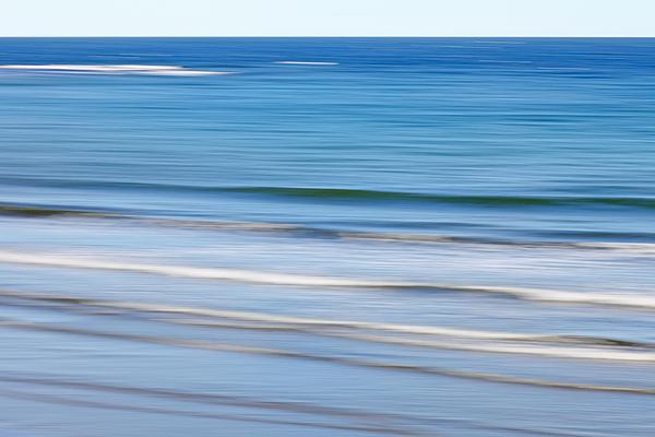 Soft waves on ocean beach (blurred) Photograph by Rainer Grosskopf