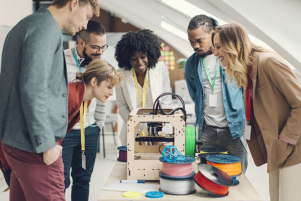 Start-Up Business Team Looking At 3D Printer. Photograph by Vgajic