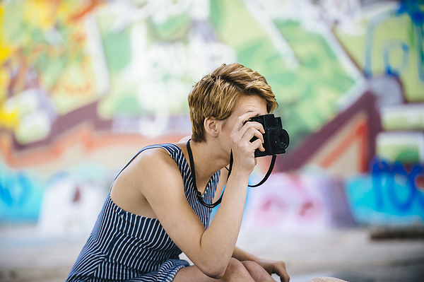 Stylish teenage girl photographing with camera in front of graffiti wall Photograph by Pete Saloutos