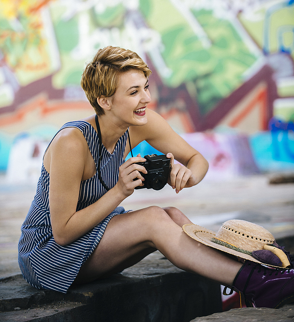 Stylish teenage girl sitting on sidewalk with camera in front of graffiti wall Photograph by Pete Saloutos