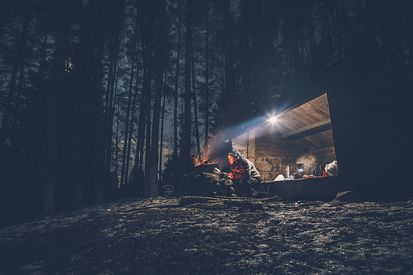 Sweden, Sodermanland, man at shelter with campfire at night Photograph by Westend61