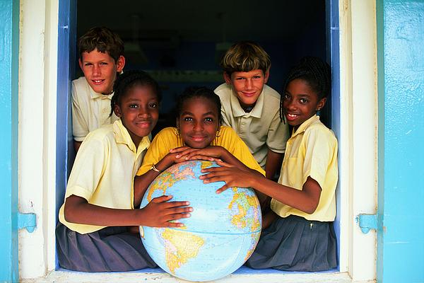 Teenage boys (12-14) posing around large globe Photograph by John P Kelly