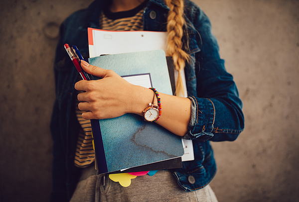 Teenage girl holding books, notebooks and pencils standing against wall Photograph by Wundervisuals