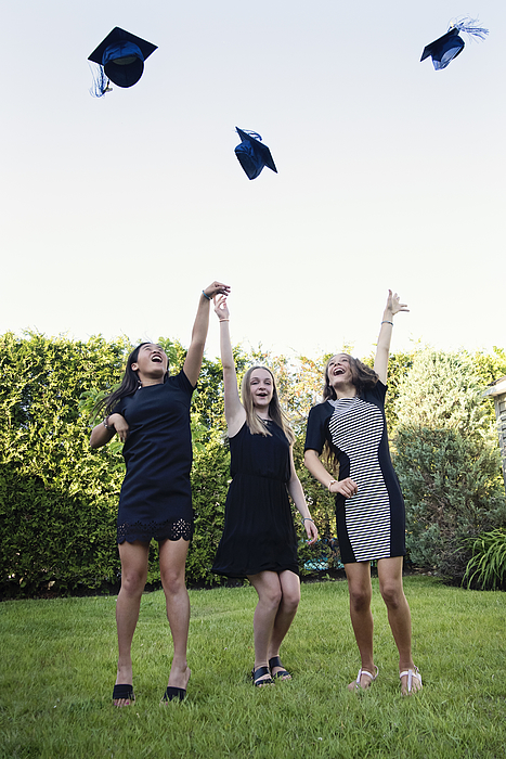 Teenage girls throwing graduation hats in backyard. Photograph by Martinedoucet