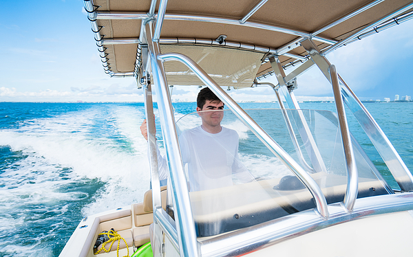 Teenager driving a boat Photograph by Thepalmer