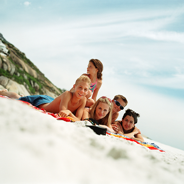 Teenagers Lying On Beach Towels At The Seashore Photograph by Patrick Sheandell OCarroll