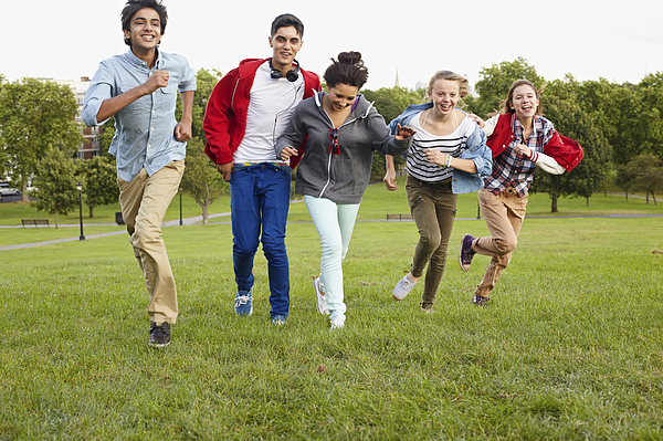 Teenagers running in a park Photograph by Image Source