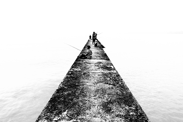 TELUK PELANDUK, MALAYSIA - 24TH DEC 2017; People cast the fishing rod to the sea. Black and white for classic view on old jetty. The old jetty still use for fisherman on fishing activities. Photograph by Shaifulzamri