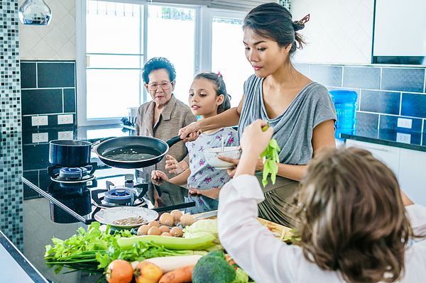 Thai family portrait having fun at the joint cooking. Modern style interior of kitchen. Photograph by Itsskin
