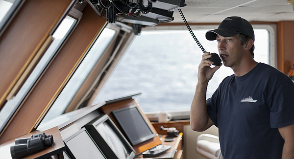 The captain uses a radio from the bridge of a boat Photograph by Noel Hendrickson