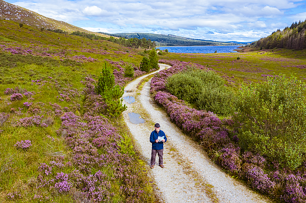 The high angle view of an active senior man looking at a map while standing on a dirt road in a remote part of Dumfries and Galloway, south west Scotland Photograph by JohnFScott