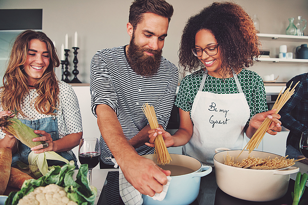 Three friends cooking spaghetti Photograph by FlamingoImages